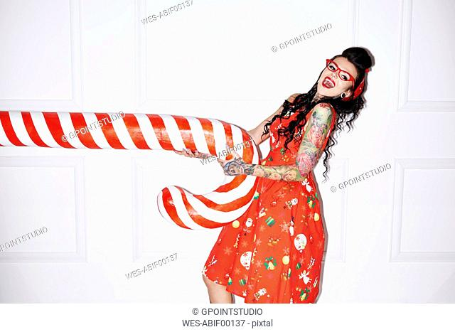 Portrait of tattooed woman having fun with oversized candy cane
