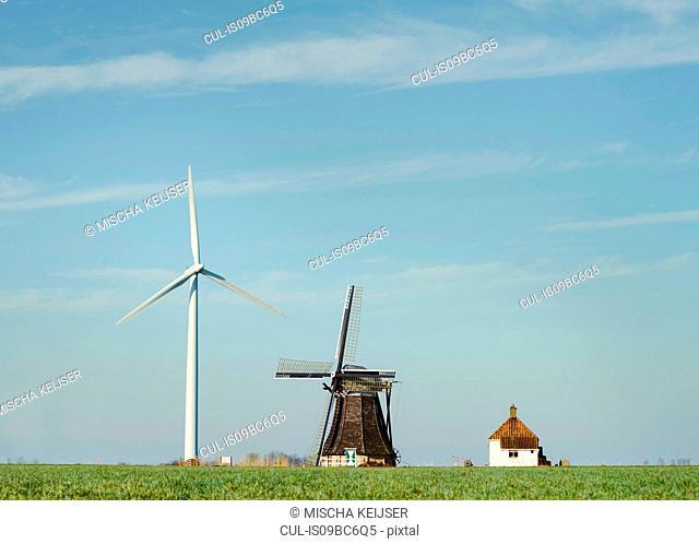 Modern wind turbine and traditional Dutch windmill stand together, Workum, Friesland, Netherlands