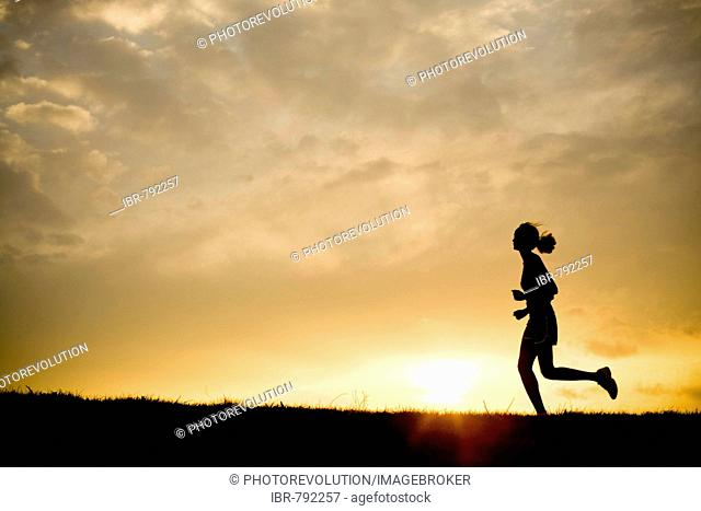 Silhouette of a woman jogging at sunset