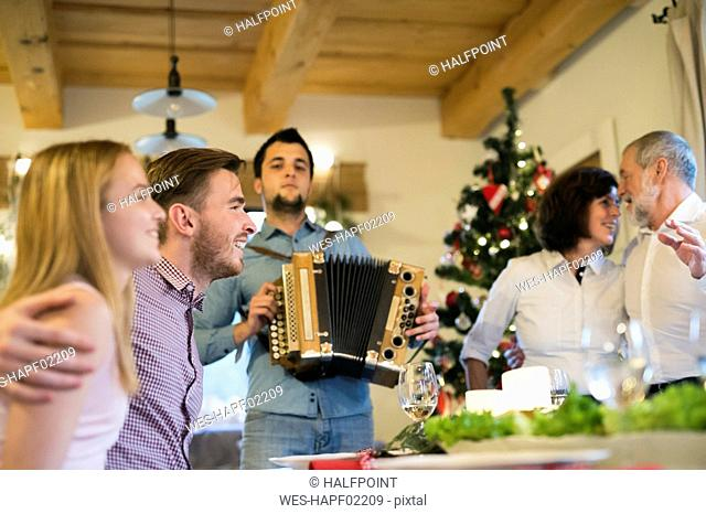 Young man playing accordion for family at Christmas