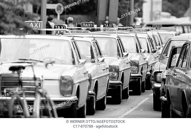 Seventies, black and white photo, road traffic, cab stand with many cabs CaptionWriter