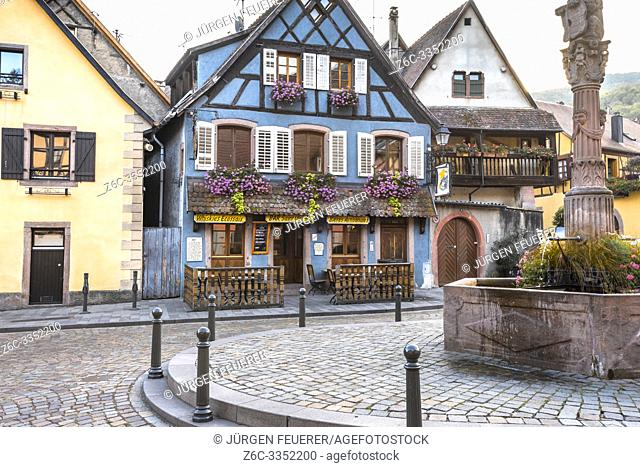 old timbered houses in the village Ribeauvillé, Alsace Wine Route, France, colorful houses around a well