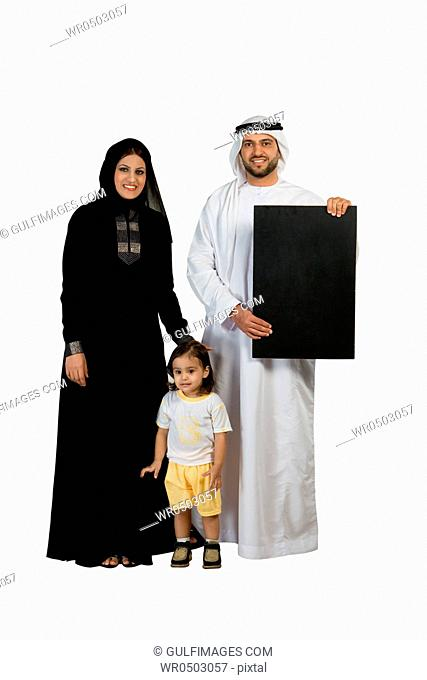 Arab family with placard, smiling, looking at the camera