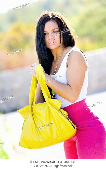 Teen girl with Yellow handbag looking for something inside