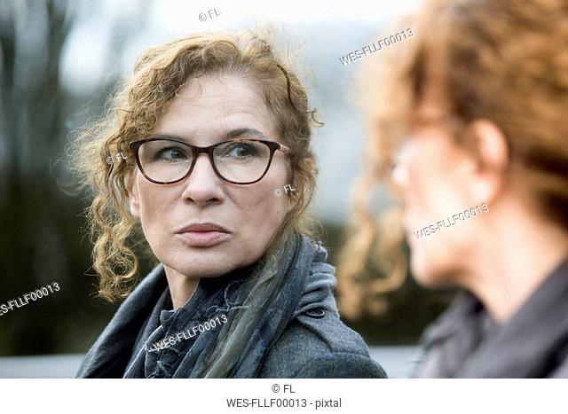 Portrait of mature woman, pensive, mirror image