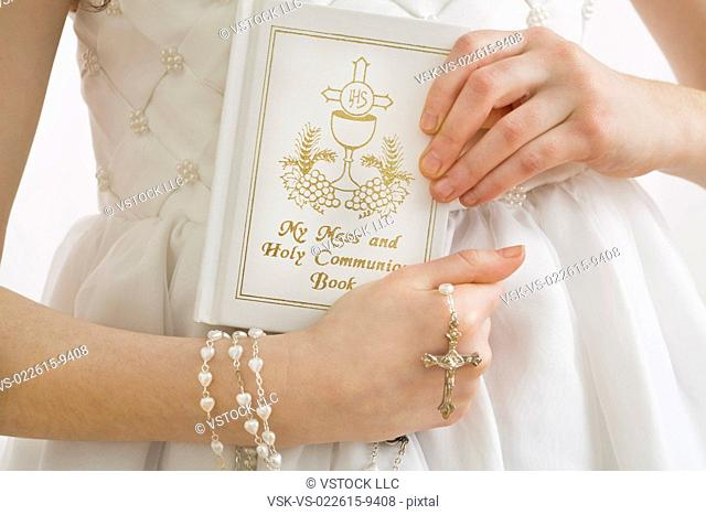 Mid-section of girl (8-9) holding rosary beads and book