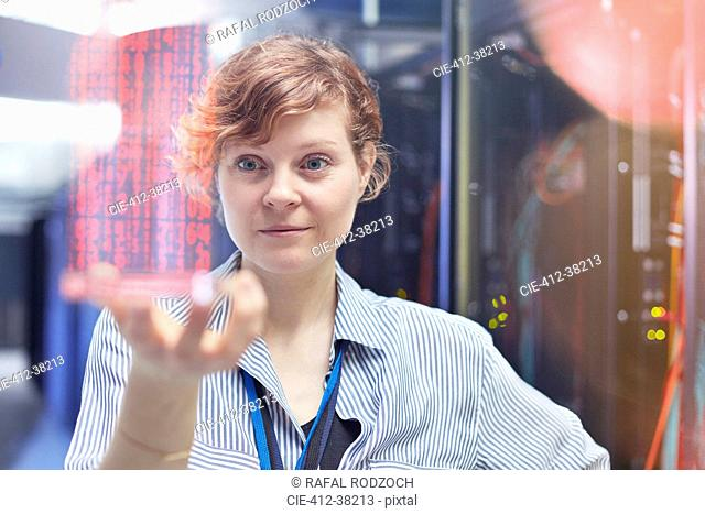 Female IT technician holding futuristic digital tablet in server room