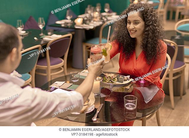 couple chinking glasses in restaurant, Vegan Oriental, Kismet, in Munich, Germany