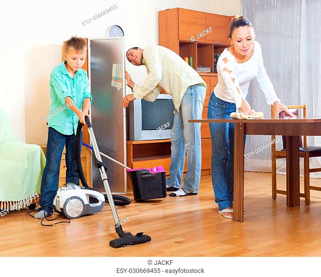 Adult couple with teenage son doing house cleaning at home