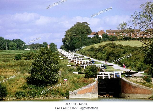 Waterway. Caen Hill. Devises Flight of locks. Water level management. Series of water chambers. White horizontal gates. View up slope of hill