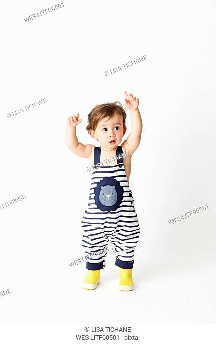 Toddler wearing striped dungarees and yellow rain boots standing in front of white background