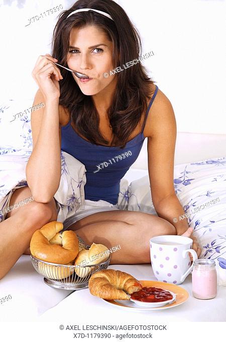 young brunette woman having breakfast in bed