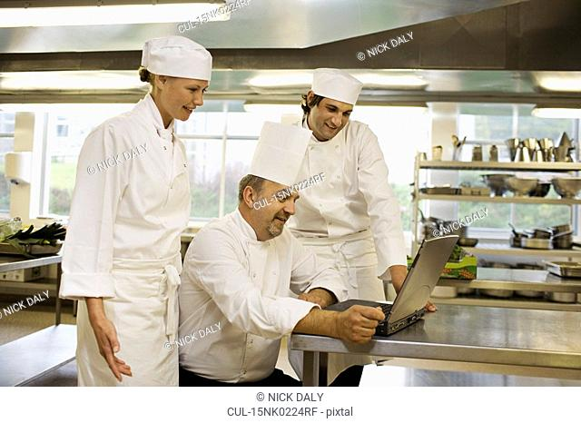 Three chefs looking at a laptop