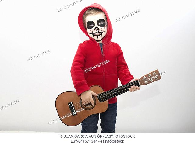 Little boy costumed as protagonist of Coco movie. Isolated over white