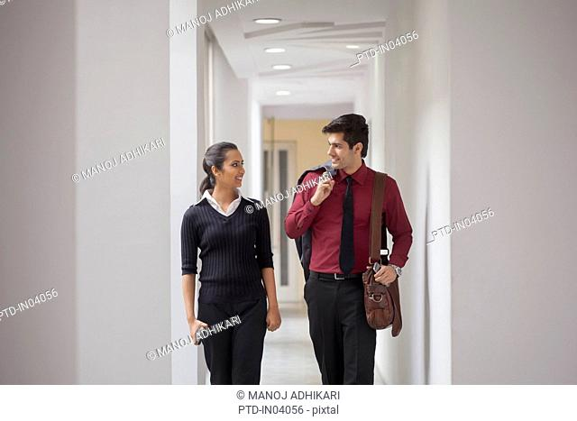 India, Two colleagues walking down corridor