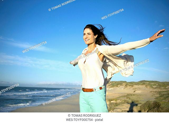 South Africa, smiling woman with outstretched arms standing on the beach