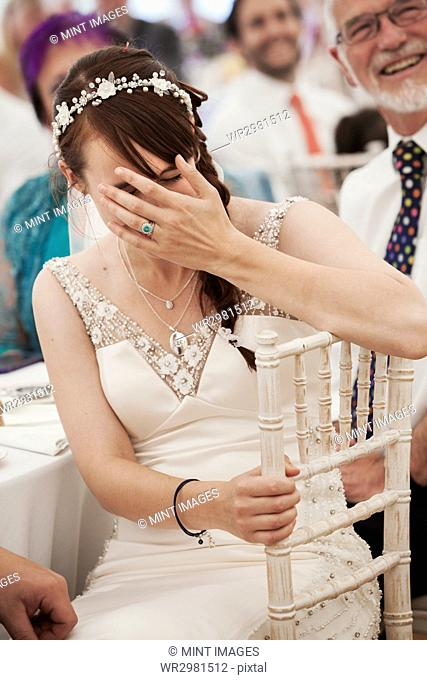 Bride in her wedding dress sitting in a marquee, laughing and covering her face