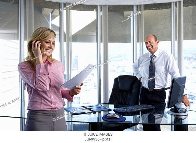 Mature businessman by desk smiling at young businesswoman on telephone holding paperwork