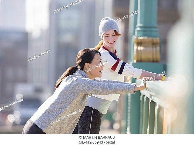 Smiling female runners stretching and talking at sunny urban railing