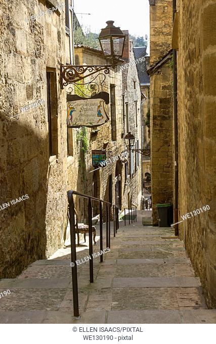 Steps going down narrow cobblestone street between sandstone buildings in charming Sarlat, Dordogne region of France
