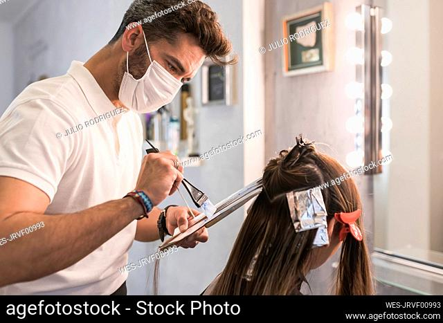 Male hairdresser with protective face mask dyeing customer's hair at salon