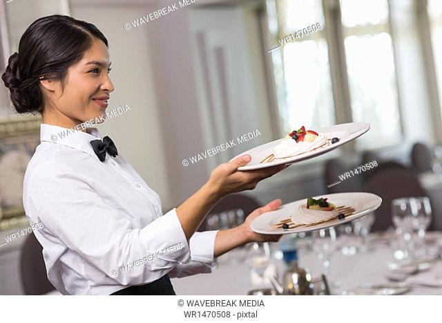 Pretty waitress holding two dessert plates