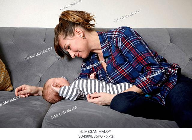 Mother on sofa looking at sleeping baby boy, smiling
