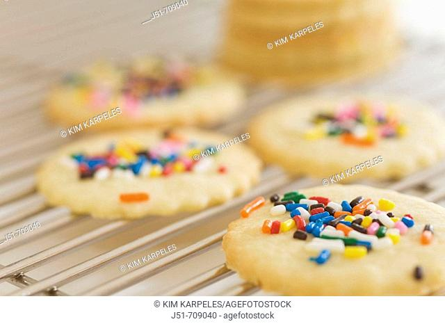 Christmas holiday sugar cookies with sprinkles pile on cooling rack