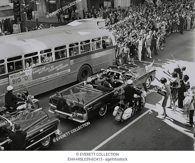 Dallas crowds waving as President Kennedy's limousine drives through downtown Dallas. Texas Governor John Connally and his wife ride in the limousine's jump...