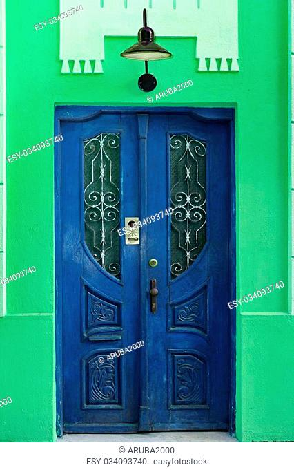 Green House Wall Fragment With Retro Blue Wooden Door And Old Hanging Lamp, Carved Door Have Intercom System And Window With Lattice
