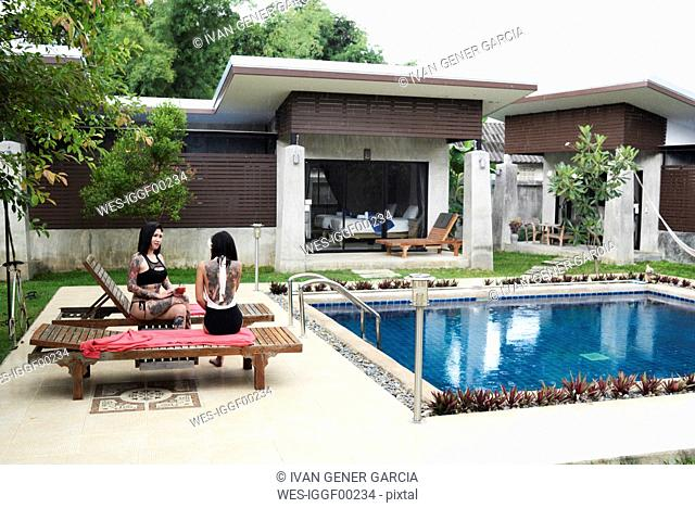 Two women sitting on sun loungers at swimming pool