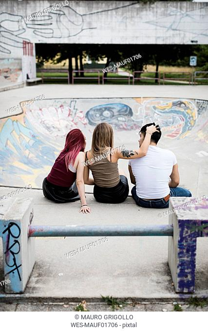Rear view of friends sitting in skatepark