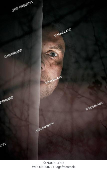 Man peeking from behind windowpane