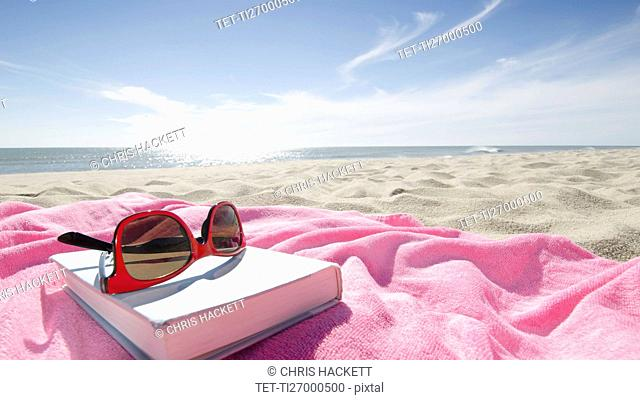 Book and sunglasses on pink towel on sandy beach
