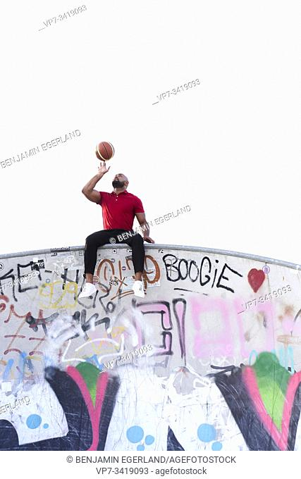 Athletic man spinning basketball on fingers. Frankfurt, Germany