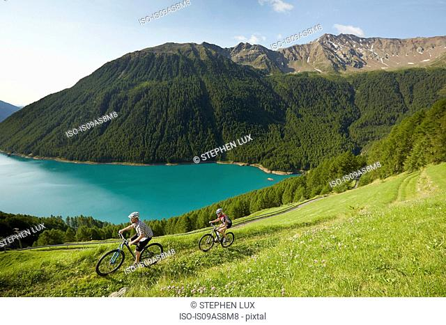 Young couple mountain biking at Vernagt reservoir, Val Senales, South Tyrol, Italy