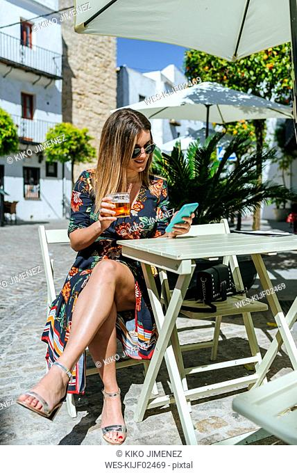 Spain, Cadiz, Vejer de la Frontera, young woman sitting at street cafe with glass of beer looking at phone