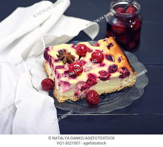 piece of cheesecake with cherry berries on a glass plate, behind a jar of canned cherries