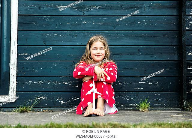 Girl wearing bathrobe outdoors sitting at wooden hut with toy wind turbine
