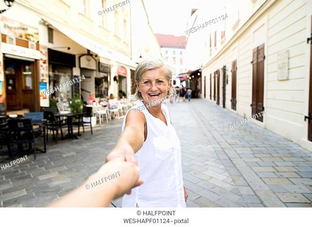 Slovakia, Bratislava, portrait of happy senior woman holding man's hand on the street