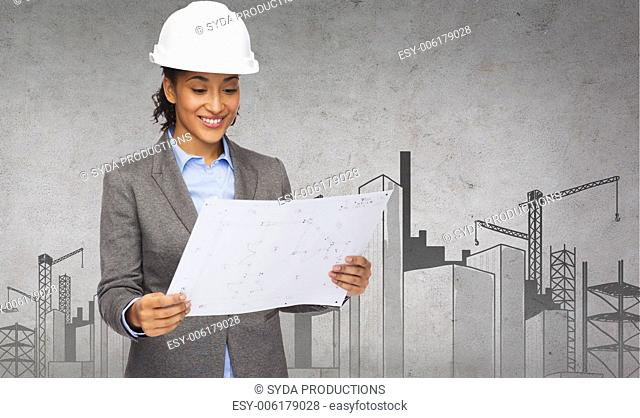 building, developing, construction and architecture concept - smiling businesswoman in white helmet looking at blueprint