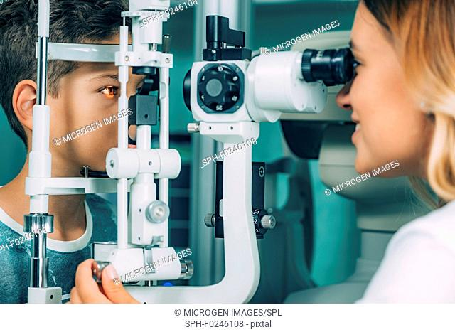 Ophthalmologist examining boy's eyes with a slit lamp