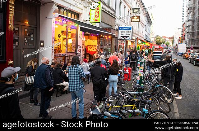 """13 September 2021, Hamburg: Numerous people stand in a queue in front of the bar """"""""Wunderbar"""""""" to get vaccinated against the coronavirus as part of the campaign..."""