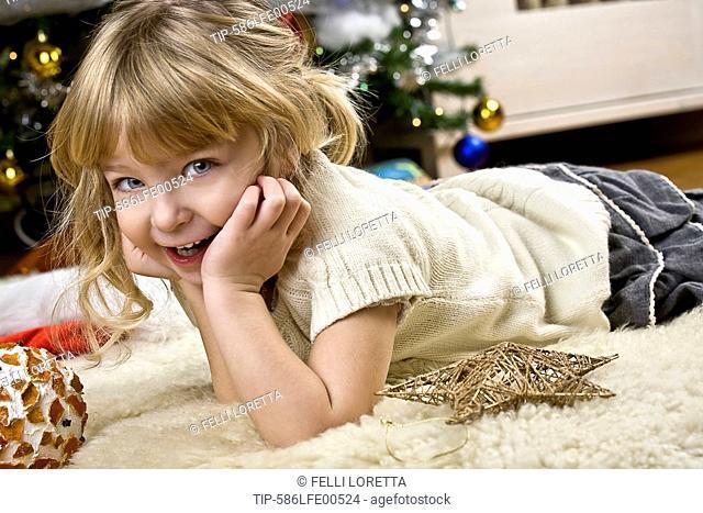 girl laying on white rug near Christmas tree