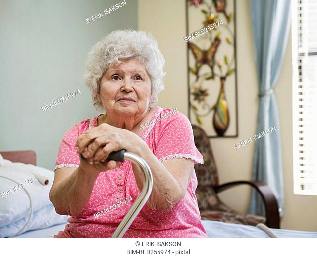Serious Caucasian woman sitting on bed leaning on cane