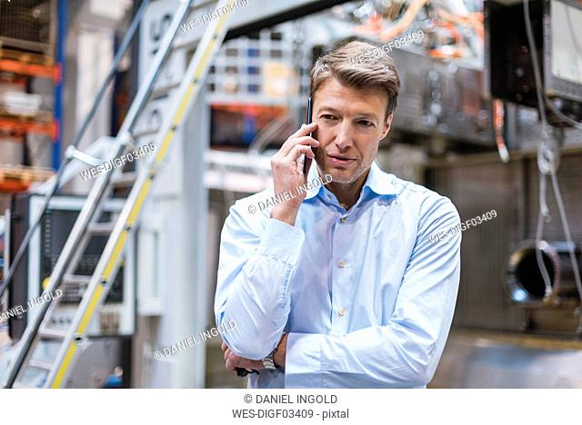 Businessman on cell phone in factory