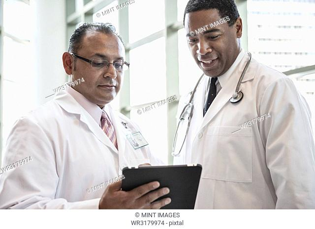 Black and Hispanic male doctors discussing a case in a hospital hallway