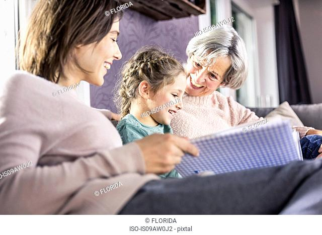 Senior woman, daughter and granddaughter reading file on sofa