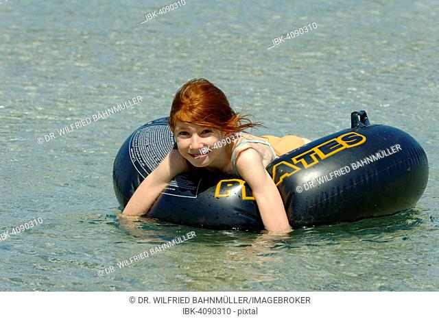 Girl in a big floating tyre in the turquoise waters in the Bay of Rondinara, southeast coast, Corsica, France