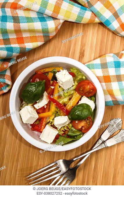 mediterranean salad with red and yellow paprika stripes, goat cheese cubes, cherry tomatoes and basil in a bowl